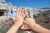 Honeymoon on Santorini island - hands with wedding rings over pa — Stok fotoğraf
