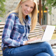 Beautiful woman sitting on bench in park with laptop — Stock Photo #51516579