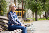 Young attractive daydreaming woman sitting in park — Stockfoto