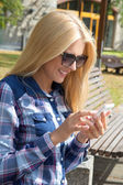 Beautiful woman using smartphone in park — Stockfoto