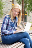 Beautiful woman sitting on bench in park with laptop — Stock Photo