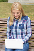 Teenage girl sitting on bench in park with laptop — Stockfoto