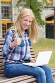 Teenage girl sitting in park with laptop and thumbs up — Stockfoto