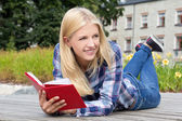 Beautiful woman lying in park with book — Stock Photo