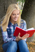 Beautiful woman sitting in park and reading book — Stockfoto