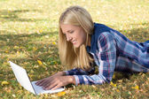 Beautiful woman lying in autumn park and using laptop — Stockfoto
