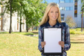 Beautiful woman showing clipboard with copyspace in autumn park — Stockfoto