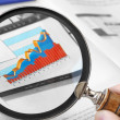 Magnifying Glass Over Financial Graph — Stock Photo