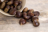 Chestnuts on wooden background — Stock Photo