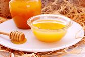 Honey dripper and jar of honey — Stock Photo