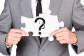 Businessman showing jigsaw connect create question mark — Stock Photo