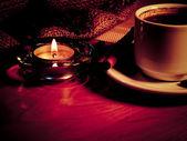 Natt bakgrund med en kopp kaffe, ljus och kaffebönor — Stockfoto