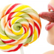 Woman sucking cute sweet candy closeup lips tongue isolated on w — Stock Photo