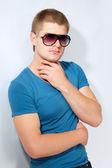 Homme jeune bel athlète avec lunettes de soleil et t-shirt bleu — Photo