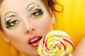 Woman licks candy with beautiful make-up — Stock Photo