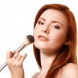 Portrait of beautiful young redheaded woman with makeup brush. — Stock Photo