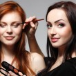 Portrait of beautiful young redheaded woman with esthetician making makeup eye shadow — Stock Photo