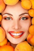 Summer portrait of young healty smiling attractive woman with ripe big fresh peaches and apricots — Stock Photo