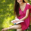 Cheerful attractive student teen girl reading book outdoor — Stock Photo