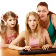 Mother with daughters looking with interest in monitor — Stock Photo