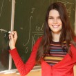 Beautiful teen girl high achiever in classroom near desk happy smiling and writing formulas of higher mathematics — 图库照片