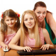 Mother with two daughters looking with different emotions in monitor — Stock Photo
