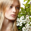 Beautiful young blond woman with spring flowers — Stock Photo