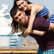 Young beautiful caucasian couple piggyback in yacht club — Stockfoto