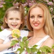 Happy mother with little daughter licks candy spring park outdoor — Foto de Stock   #33646507