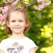 Portrait of happy little girl near Japanese cherry tree — Stock Photo