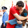 Stock Photo: Young couple hugs and kiss - first love, 1 May parade, march of proletariat, Odessa, Ukraine, 01 May 2012