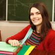 Foto Stock: Beautiful teen girl high achiever in classroom over desk happy smiling