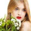 Beautiful young blond woman with spring flowers — Stock Photo #33646973