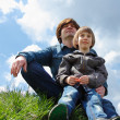 Happy father with little son sitting on green grass and looking in future — Stock Photo
