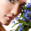 Beautiful teen girl smell and enjoy fragrance of snowdrop flower — Stock Photo