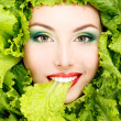 Woman beauty face with green fresh lettuce leaves frame — Stock Photo