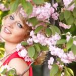 Beautiful young woman enjoying near blooming Japanese cherry tree — Stock Photo