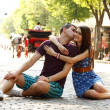 Love story of young couple sitting on stone paving hug and kiss — Stok fotoğraf