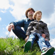 Happy father with little son sitting on green grass and looking in future — Stock Photo #33647613