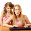 Teen and child girls looking with interest in monitor — Stock Photo