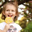 Happy little girl licks sweet candy nature spring outdoor — Stock Photo