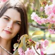 Beautiful young woman in spring blooming garden — Stock Photo