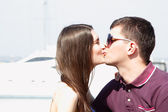 Young beautiful caucasian couple hugs and kiss in yacht club — Foto Stock