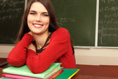 Beautiful teen achiever in classroom near desk happy smiling — Stok fotoğraf