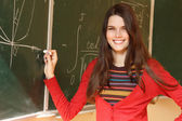 Beautiful teen girl high achiever in classroom near desk happy smiling and writing formulas of higher mathematics — Стоковое фото