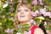 Beautiful woman enjoying near blooming Japanese cherry tree — Stock Photo