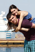 Young beautiful caucasian couple piggyback in yacht club — Stock Photo