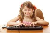 Little girl playing with keyboard looking at camera like in monitor — Stock Photo