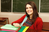 Beautiful teen girl high achiever in classroom over desk happy smiling — ストック写真