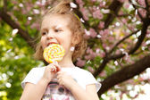 Happy little girl licks sweet candy nature outdoor — Stock Photo